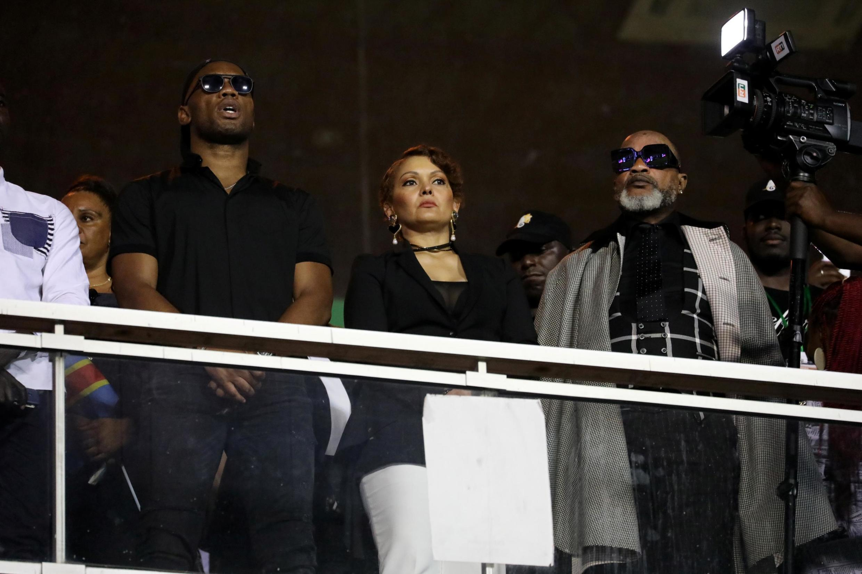 Le chanteur congolais Koffi Olomide et sa femme au côté du joueur de foot Didier Drogba dans une tribune du stade d'Abidjan, vendredi 30 août.
