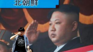 Gente camina frente a un monitor mostrando al líder de Corea del Norte, Kim Jong Un, en un reporte de noticias sobre el anuncio de los ensayos nucleares, en Tokyo, Japón, el 21 de abril de 2018.