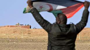 A Sahrawi holds aloft a Polisario flag under the watchful eyes of Moroccan soldiers guarding an observation post on the 2,700 kilometre (1,700 mile) long wall that Rabat built to defend its control of much of the disputed Western Sahara