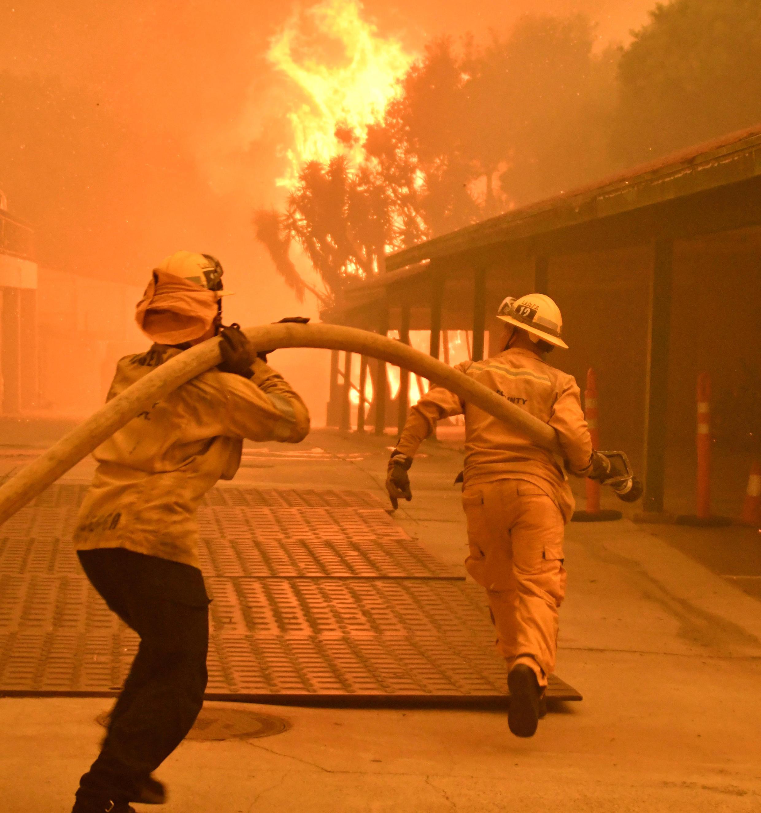 Bomberos tratando de apagar las llamas de Woolsey Fire, en una zona residencial de Malibú, California, el 9 de noviembre del 2018.