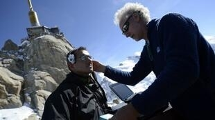President and project founder of IFREMMONT Doctor Emmanuel Cauchy (R), makes medicals tests on a man on April 17, 2013 at the top of the Aiguille du Midi (3800 m)
