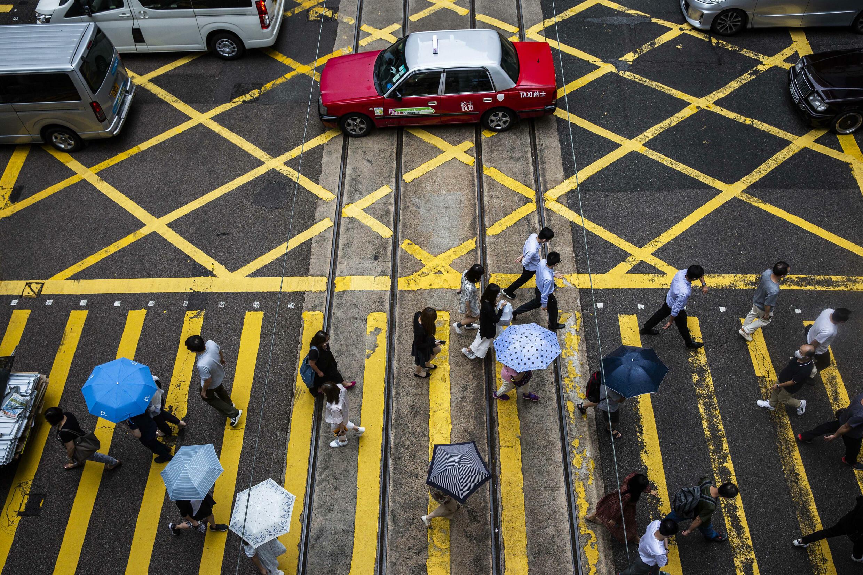 Imagen de archivo de personas con sombrilla cruzando una calle en Hong Kong, donde los concejales de distrito deben jurar lealtad a China