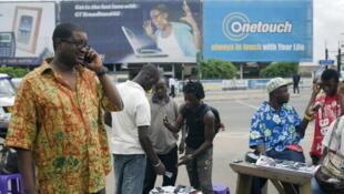 Un homme communique avec son téléphone mobile à coté des vendeurs de portables en plein air à Accra au Ghana, le 14 juin 2008.