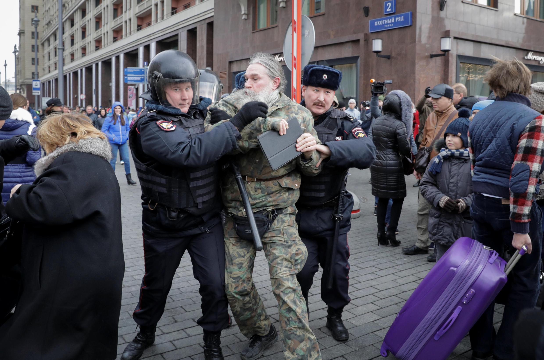 Manifestante é levado pela polícia russa no centro de Moscou, neste domingo (5).