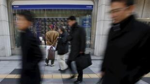 Un passant regarde les cotations à la Bourse dans une vitrine d'un courtier,à Tokyo, le 26 février 2016.