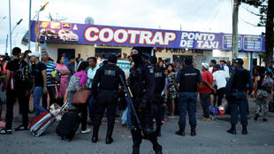 Cảnh sát chống bạo động Brazil nói chuyện với người tị nạn đến từ Venezuela tại thị trấn Pacaraima, giáp giới với Venezuela, ngày 19/08/2018.