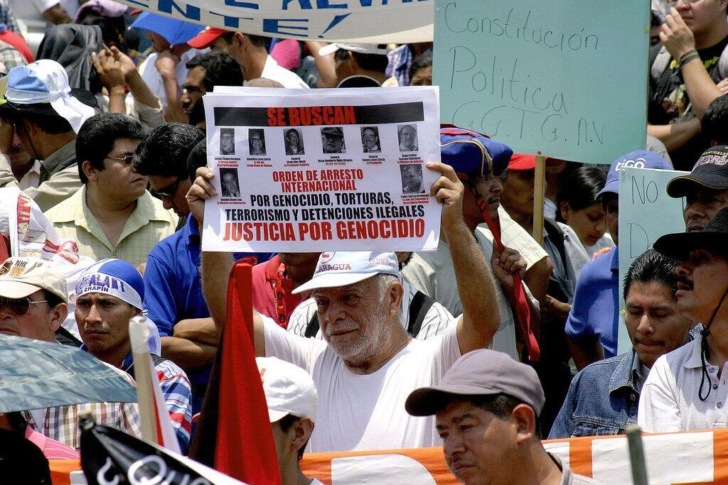 Un hombre levanta un cartel pidiendo justicia por genocidio en Guatemala, mayo de 2008.