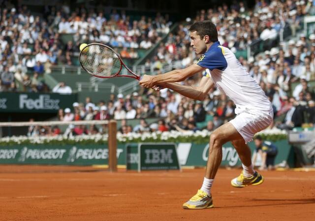 Gilles Simon of France hits a return to Roger Federer of Switzerland