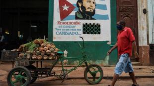 """Un hombre con una mascarilla camina cerca de un letrero con la imagen del difunto líder cubano Fidel Castro y en donde se lee """"Revolución es cambiar todo lo que debe ser cambiado"""", en La Habana el 13 de mayo de 2020, en medio de la pandemia del nuevo coronavirus.Cuba lleva dos semanas con más altas médicas que contagios y arrincona a la enfermedad pero sin bajar la guardia. Hasta el momento ha confirmado 1810 casos, con 79 fallecidos."""