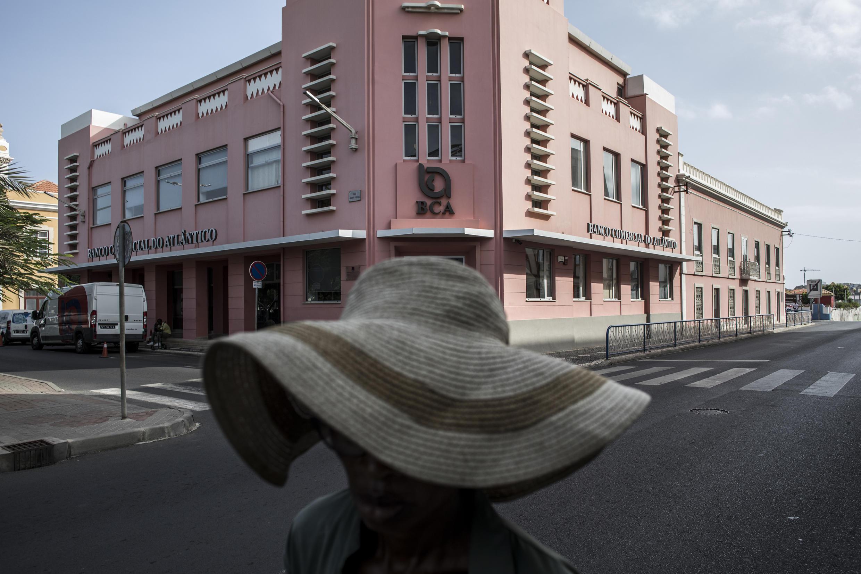 Imagem de Ilustração. Agente dos serviços de limpeza municipais, passa em frente de um banco, na cidade da Praia.