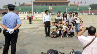 A police officer (L) stands guard as tourists take group pictures at the Tiananmen Square in front of the giant portrait of late Chairman Mao Zedong in Beijing, September 6, 2011.