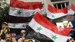 Waandamanaji nchini Syria wakiwa na bendera za nchi hiyo