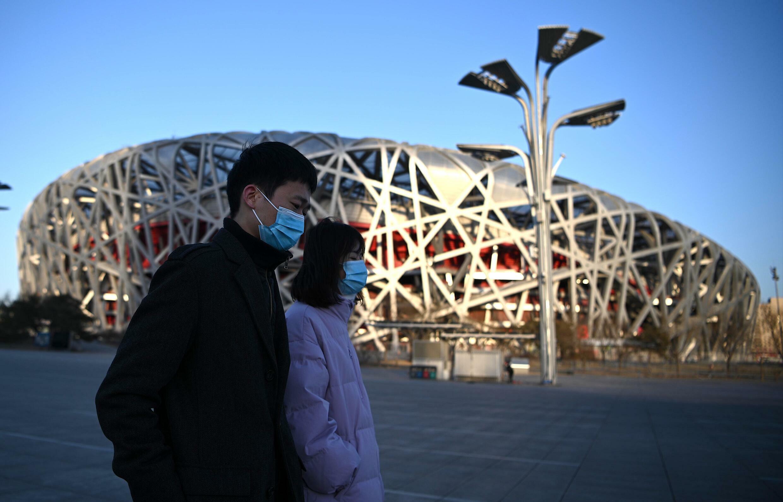"""Un couple passe devant le stade du """"Nid d'Oiseau"""", le 3 février 2021 à Pékin, où auront lieu les cérémonies d'ouverture et de clôture des Jeux Olympiques de Pékin 2022 (du 4 au 20 février)"""