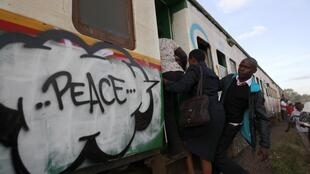 Commuters board a train painted with murals promoting peace, Nairobi, 25 February