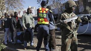A soldier stands guard as a policeman searches shoppers in Johannesburg