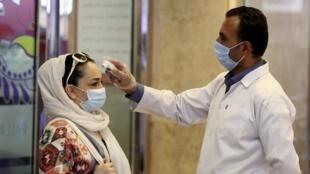 Une femme se fait vérifier sa température à l'entrée d'un centre commercial de Téhéran (image d'illustration).