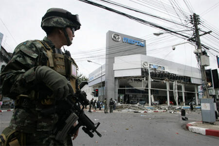 A soldier stands guard near the site of the bomb attack in Yala province.