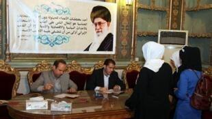 Mulheres votam nas eleições iranianas, sob um cartaz do líder Ali Khamenei.