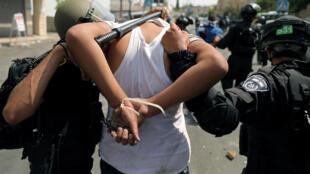 以色列警卫押走一名巴勒斯坦人