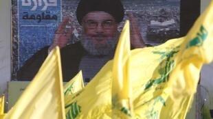 Hassan Nasrallah, le chef du Hezbollah libanais, s'adressant à ses partisans via un écran géant lors d'un rassemblement à Aita el-Chaab le 16 août 2013.