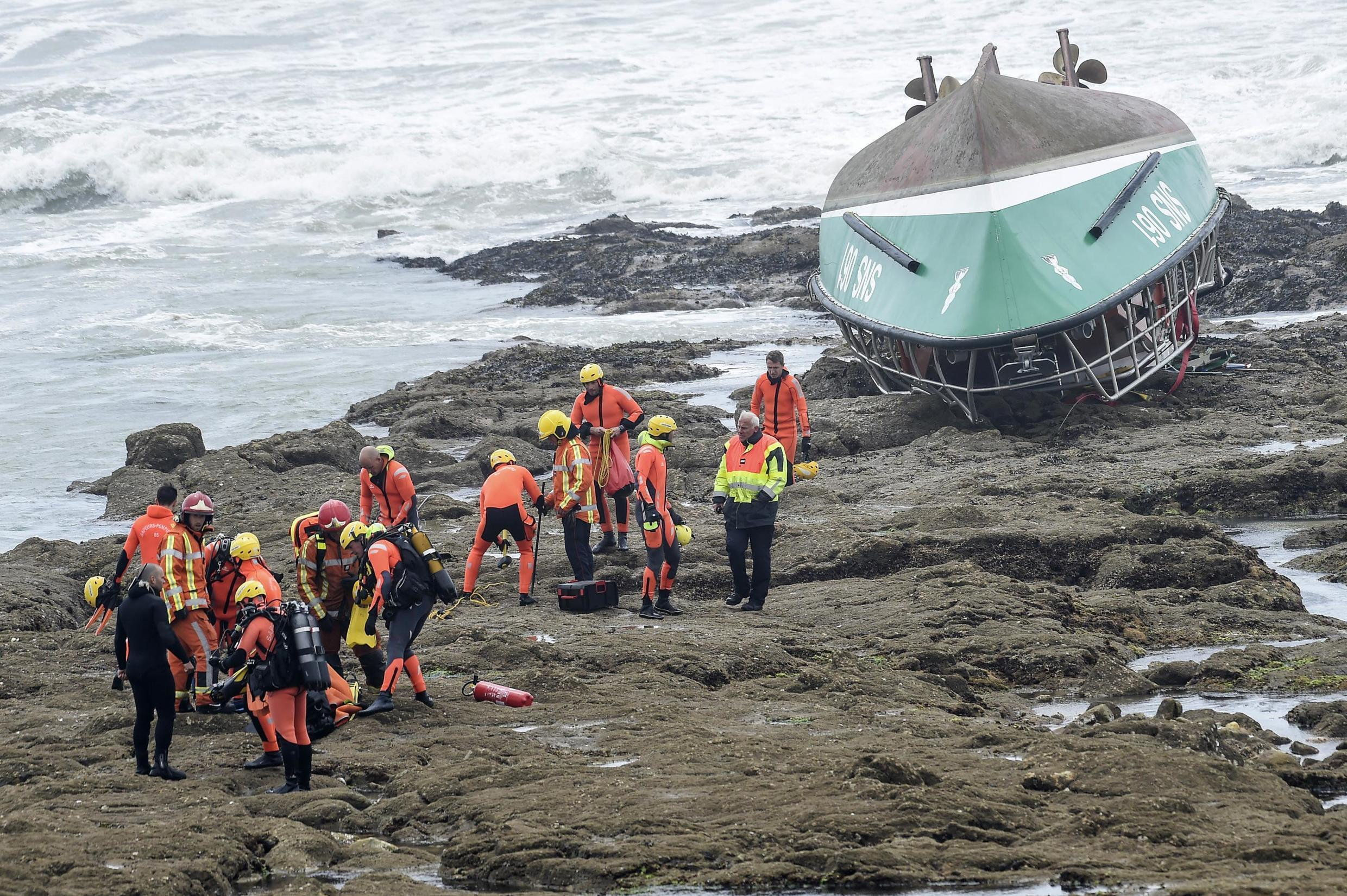 Rescuers work near the capsized boat of the National Society of Sea Rescue (SNSM) on a beach of Les Sables-d'Olonne, where three rescuers perished during storm Miguel on 7 June, 2019.