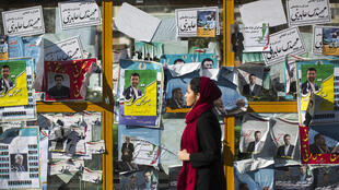 Jovem iraniana passa diante de cartazes de candidatos políticos em Teerã nesta quinta-feira (25).