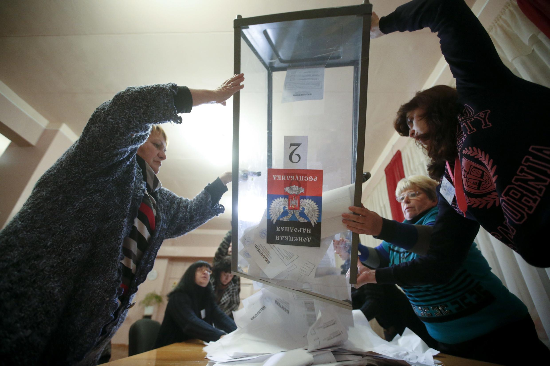 Membros de comissão eleitoral esvaziam urna para apuração dos votos na autoproclamada República Popular de Donetsk, no leste da Ucrânia.