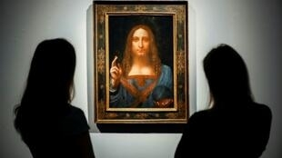 Christie's employees pose in front of a painting entitled Salvator Mundi and attributed to Leonardo da Vinci at a photocall at the auction house in central London on October 22, 2017 a month ahead of its sale