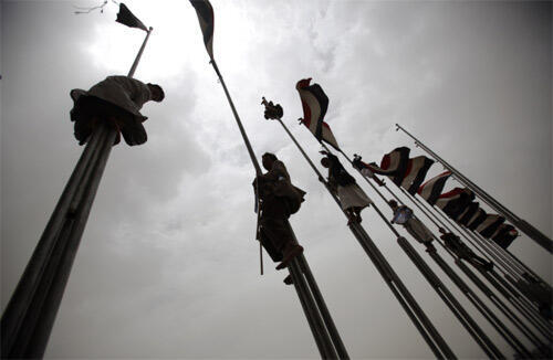 Supporters of Yemen's President Ali Abdullah Saleh climb flag poles during a rally in Sanaa on Friday