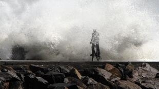 A man is drenched by a wave during high tide as he cycles past a harbour in Chennai