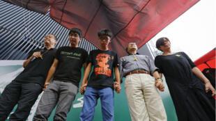 Les leaders pro-démocratie Benny Tai, Alex Chow, Joshua Wong, Alan Leong et Woo Mei Lin (de g. à d.) ont annoncé dimanche l'annulation du processus de vote en se tenant par la main.