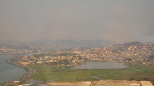 Vue du Marais Masay. Au fond, les quartiers de la capitale Antananarivo sont ensevelis par un épais nuage de pollution.