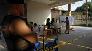Un officier monte la garde dans un bureau de vote de la province de Yala, en Thaïlande, le 24 mars 2019.