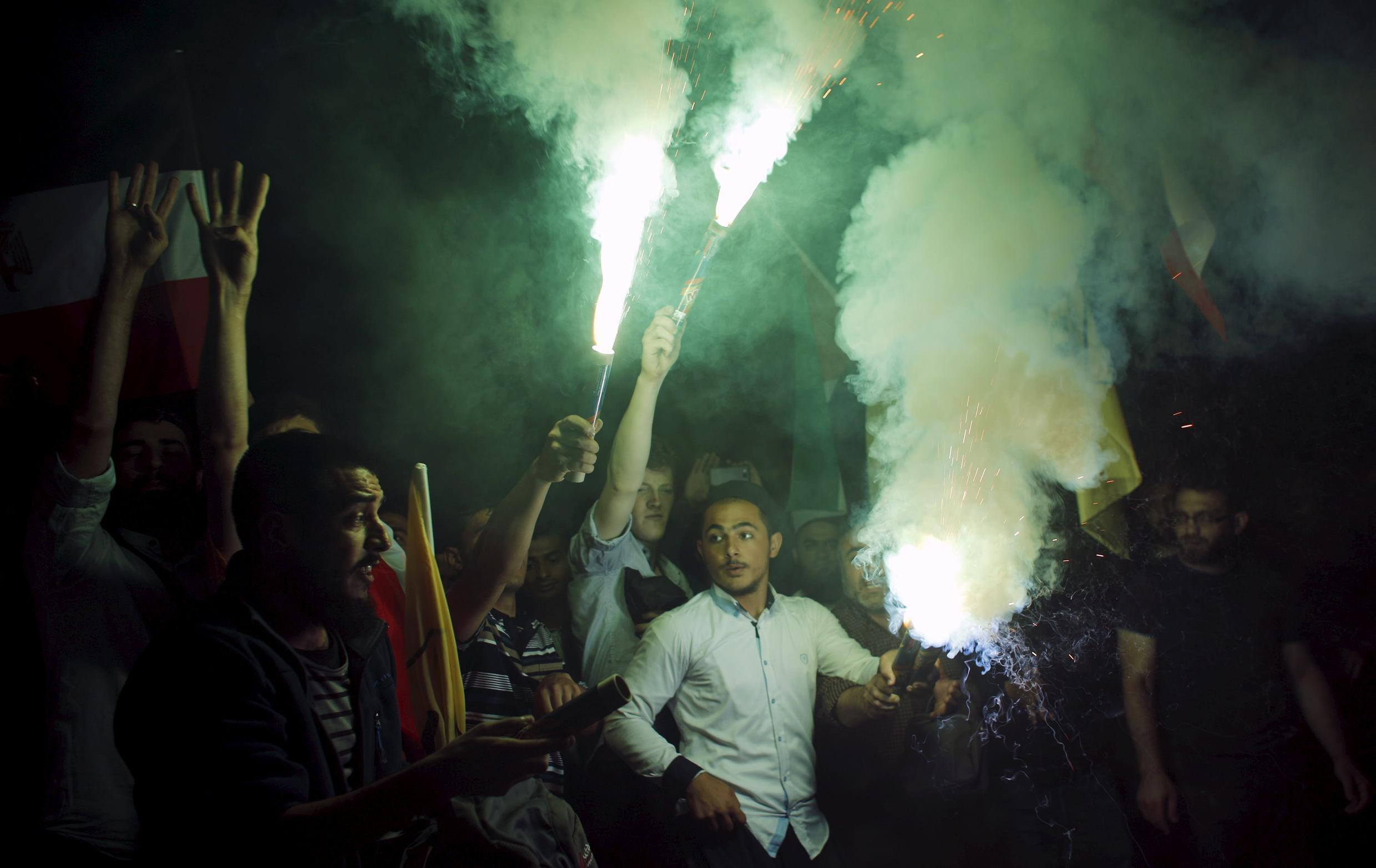 Pro-Islamists demonstrators light flares during a protest against an Egyptian court's decision to sentence deposed President Mohamed Mursi to death, in front of the Egyptian Consulate in Istanbul, Turkey, early June 17, 2015.