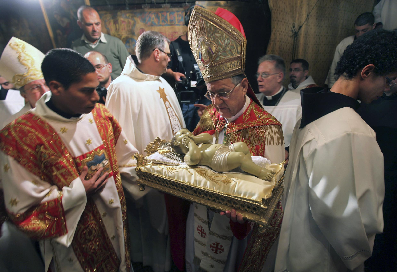 O patriarca de Jerusalém carrega a estatueta do Menino Jesus durante a Missa de Natal na Igreja de Belém.
