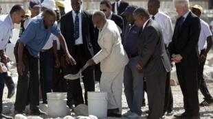 Le président haïtien, René Préval (C), en présence de Bill Clinton (D) pose la première pierre du mémorial en souvenir des victimes du tremblement de terre, le 12 janvier 2011.