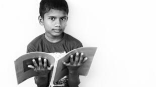 Un enfant lit un cahier.