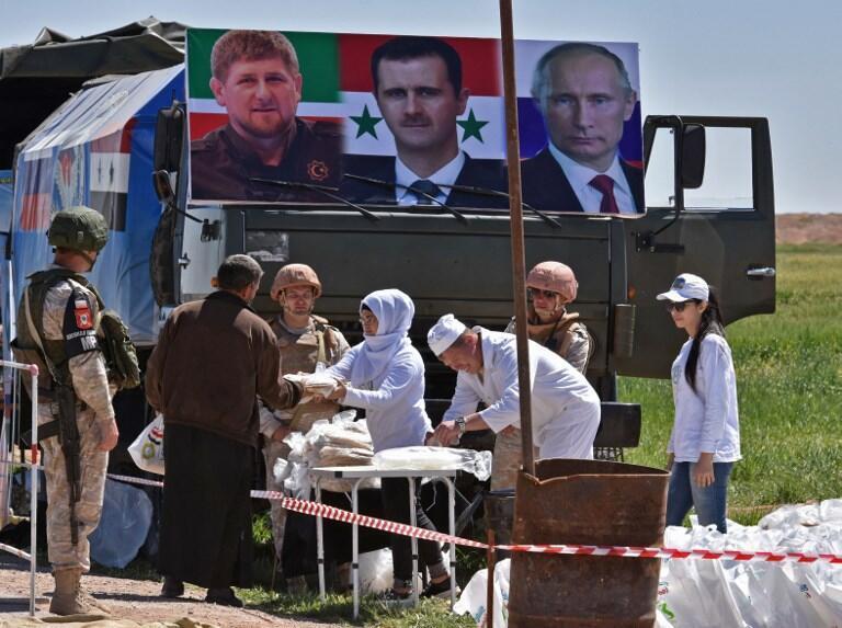 Nga và Syria phân phát lương thực, bên trên là chân dung các nhà lãnh đạo Tchechnya, Nga và Syria, tại Abu al-Duhur, ngày 04/04/2018.