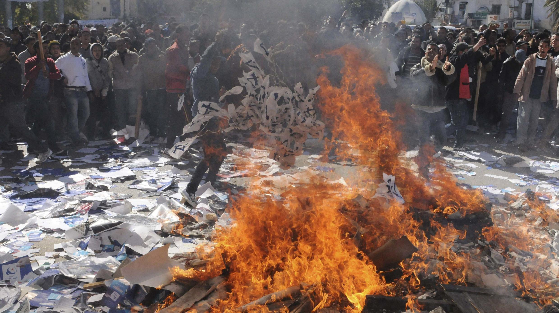 Tunisie : des manifestants brûlent des documents du parti Ennahda, à l'extérieur des locaux du parti, à Gafsa, le mercredi 6 février 2013