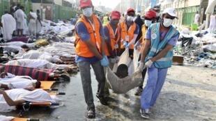 Agentes sauditas transportam corpo de uma das 717 vítimas do tumulto ocorrido ontem durante a peregrinação a Meca.