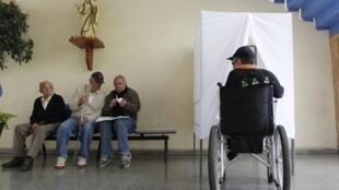 Un elector en silla de ruedas vota el domingo 28 de octubre de 2012 en Valparaíso.