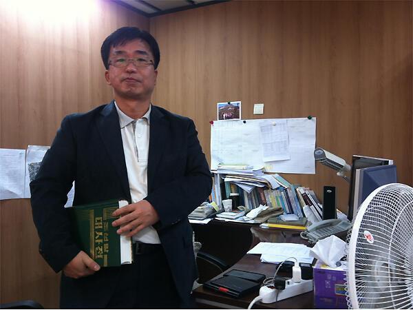 Han Youngun dirige une équipe de 30 lexicographes sud-coréens qui travaillent à la rédaction d'un dictionnaire commun entre les deux Corées. Il porte à la main un dictionnaire nord-coréen...