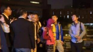 根據NOW電視新聞視頻,曾鈺成離開理大時,一名紅衣女孩與他步出校園,有傳聞指該女孩是中共高幹親戚。2019年11月18日。