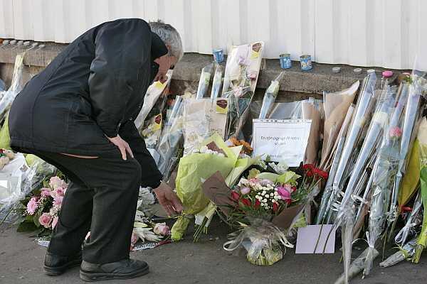Um homem deixa flores em frente a escola judaica Ozar Hatorah, em Toulouse, onde um homem matou quatro pessoas em março de 2012.