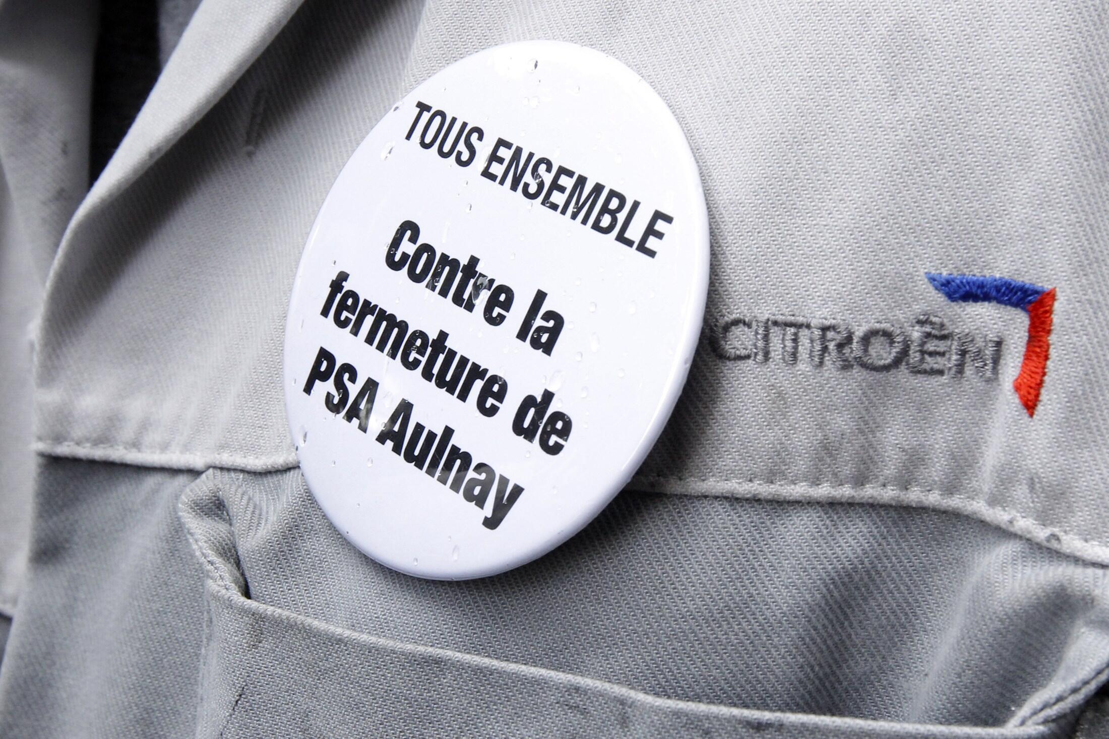"""Funcionário da Peugeot Citroen usa bottom que diz """"Todos juntos contra o fechamento da fábrica de Aulnay""""."""