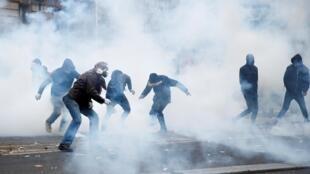 Policiais franceses usam granadas de gás lacrimogêneo para dispersar manifestantes durante protesto contra a reforma da Previdência, em Paris.