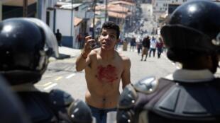 Adolescente com sangue no peito enfrenta policiais durante protesto, após o assassinato de Kluiver Roa, um estudante de 14 anos, na cidade de San Cristobal, na Venezuela.