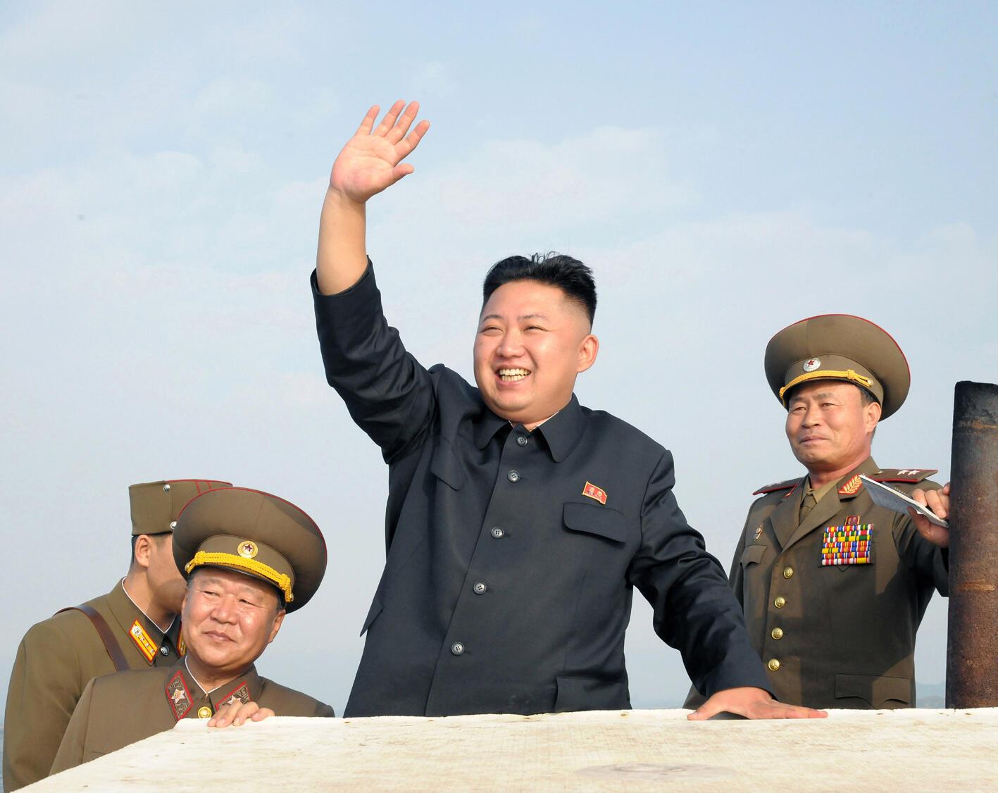 Lãnh tụ Bắc Triều Tiên Kim Jong Un (giữa) vẫy chào trong chuyến đi thăm một đơn vị quân đội đóng tại một đảo miền tây nam, ngày 19/08/2012.