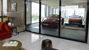 Một chiếc xe siêu sang Lamborghini Gallardo (phải) đậu trước garage thuộc một căn hộ sang trọng ở tầng 14 khu nhà Hamilton Scott ở Singapore. Chủ căn hộ phải trả tối thiểu 9,5 triệu đô la để có thêm garage riêng như thế.