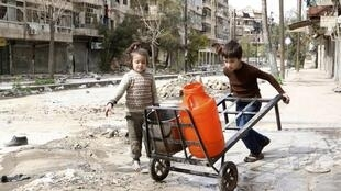 Children push a cart with water containers along a damaged street in Aleppo